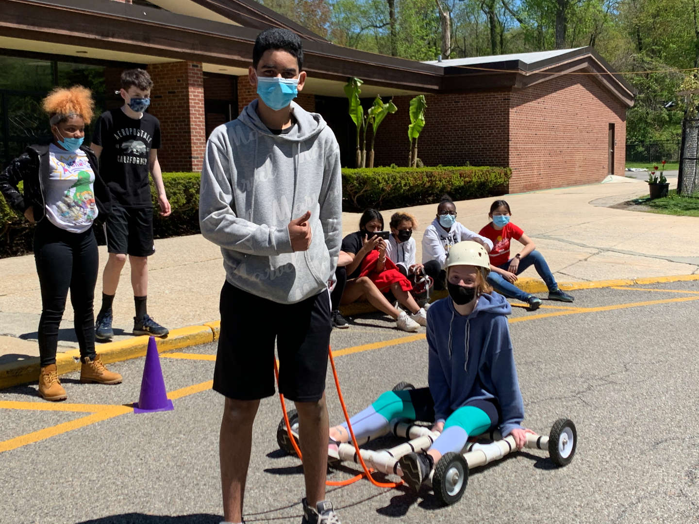 One student pulls a teammate on a go-cart the team made.
