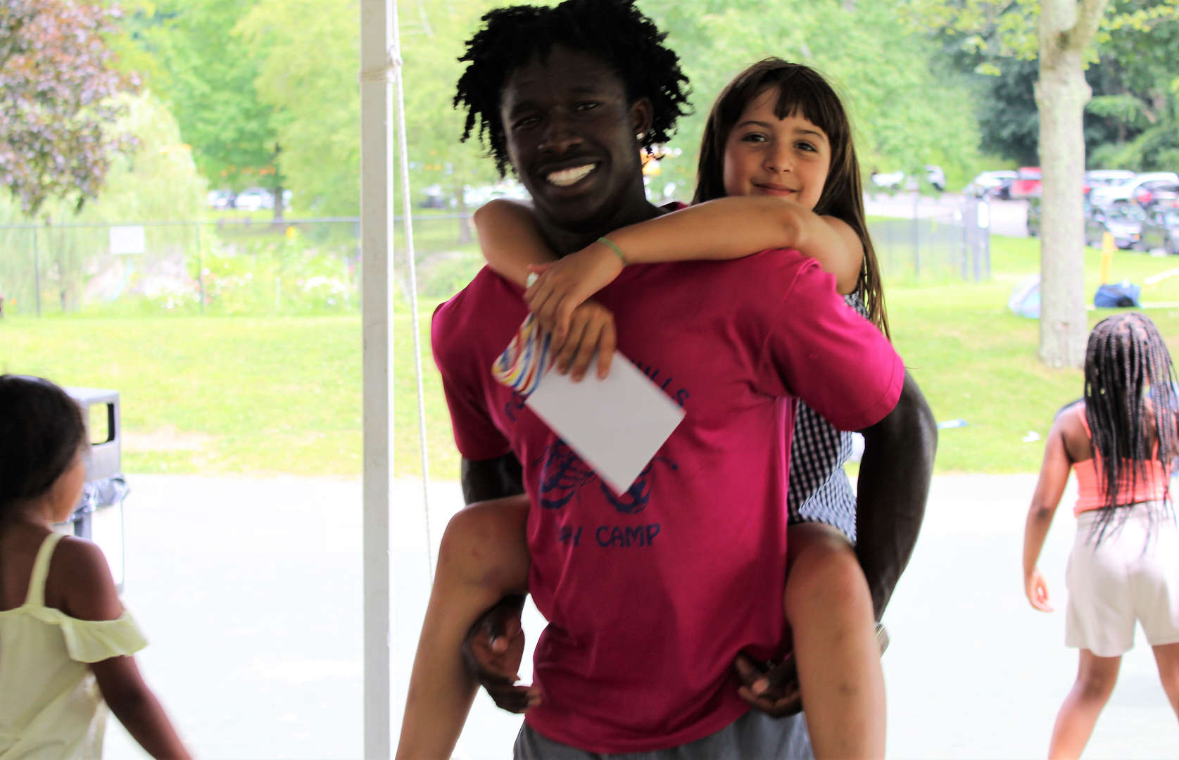 A staff member gives a piggy-back ride to a young girl attending camp.