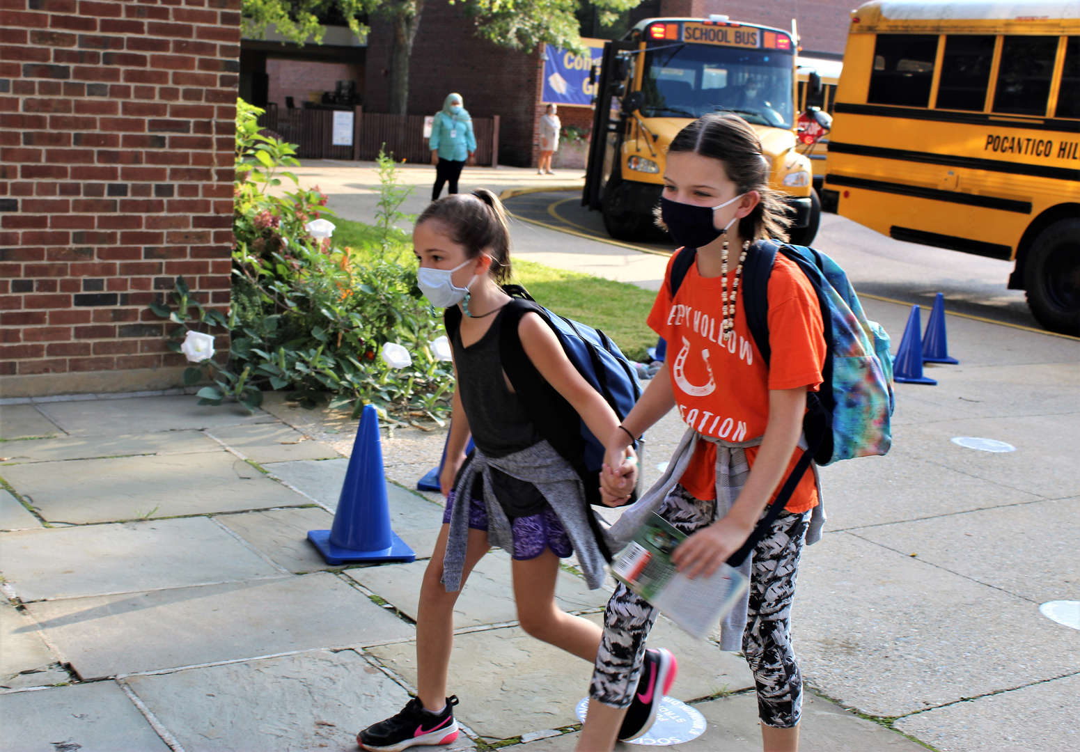 Two female students walk into school on the first day.