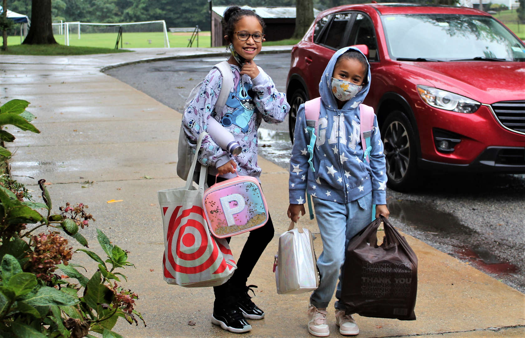 Two girls arrive at school.