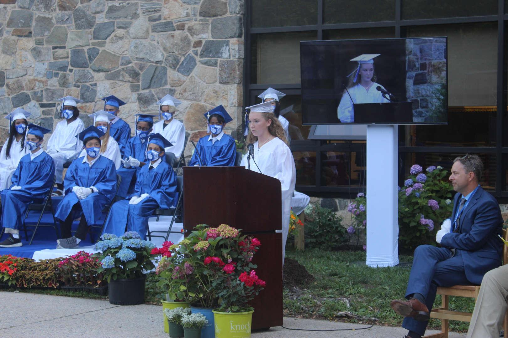 Graduate Catherine W. addresses classmates, staff and students.