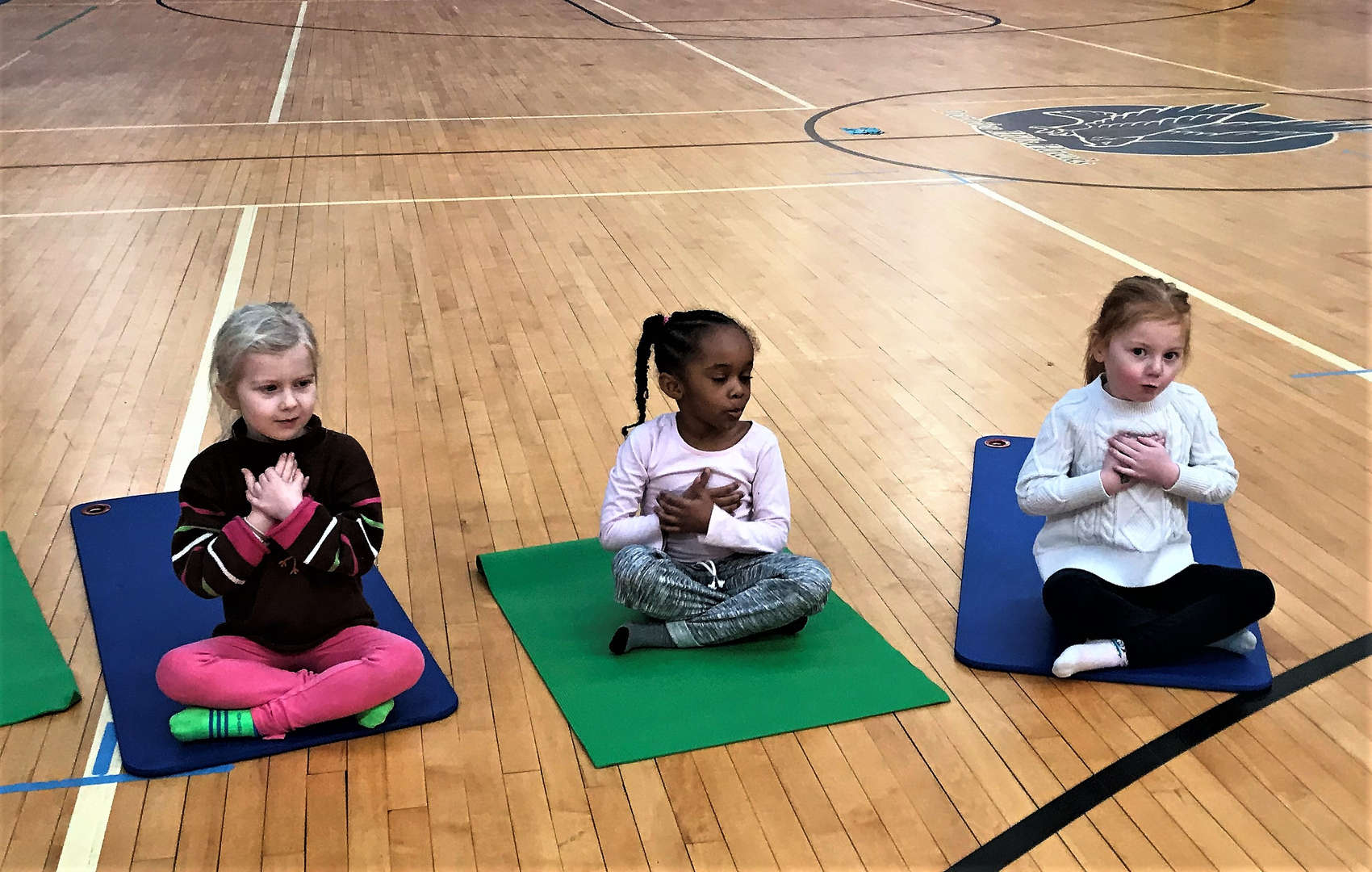Three students practice a yoga technique during a class.