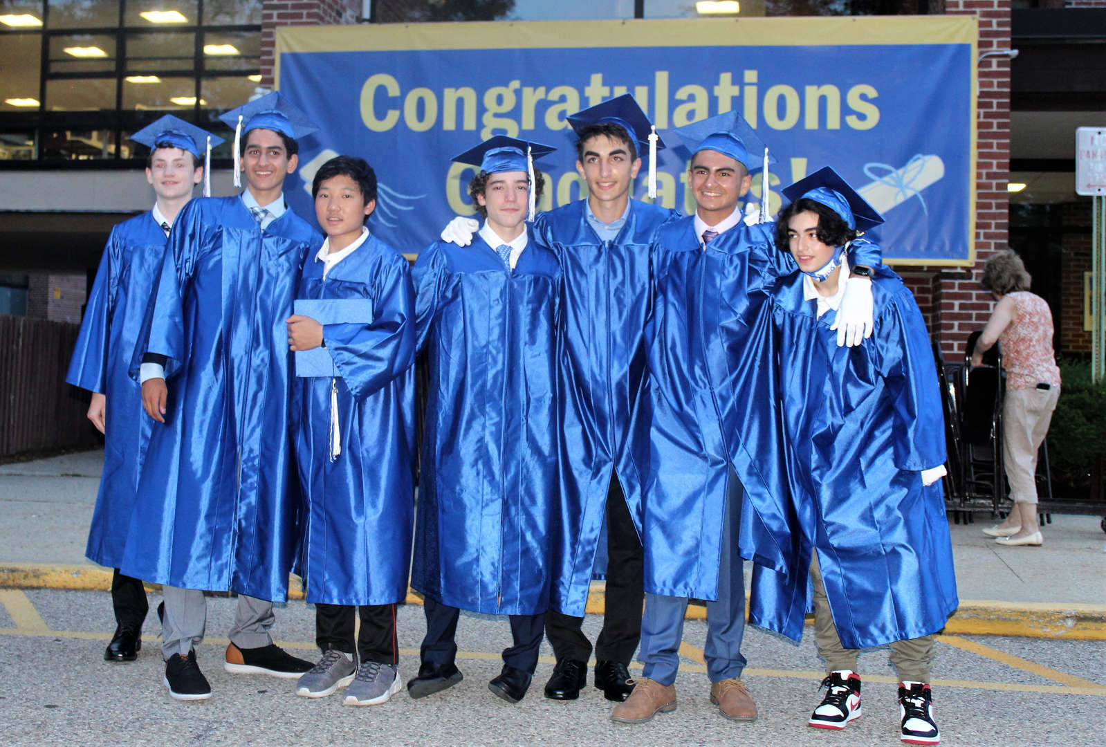 Seven boys who graduated lined up in front of a congratulations banner.