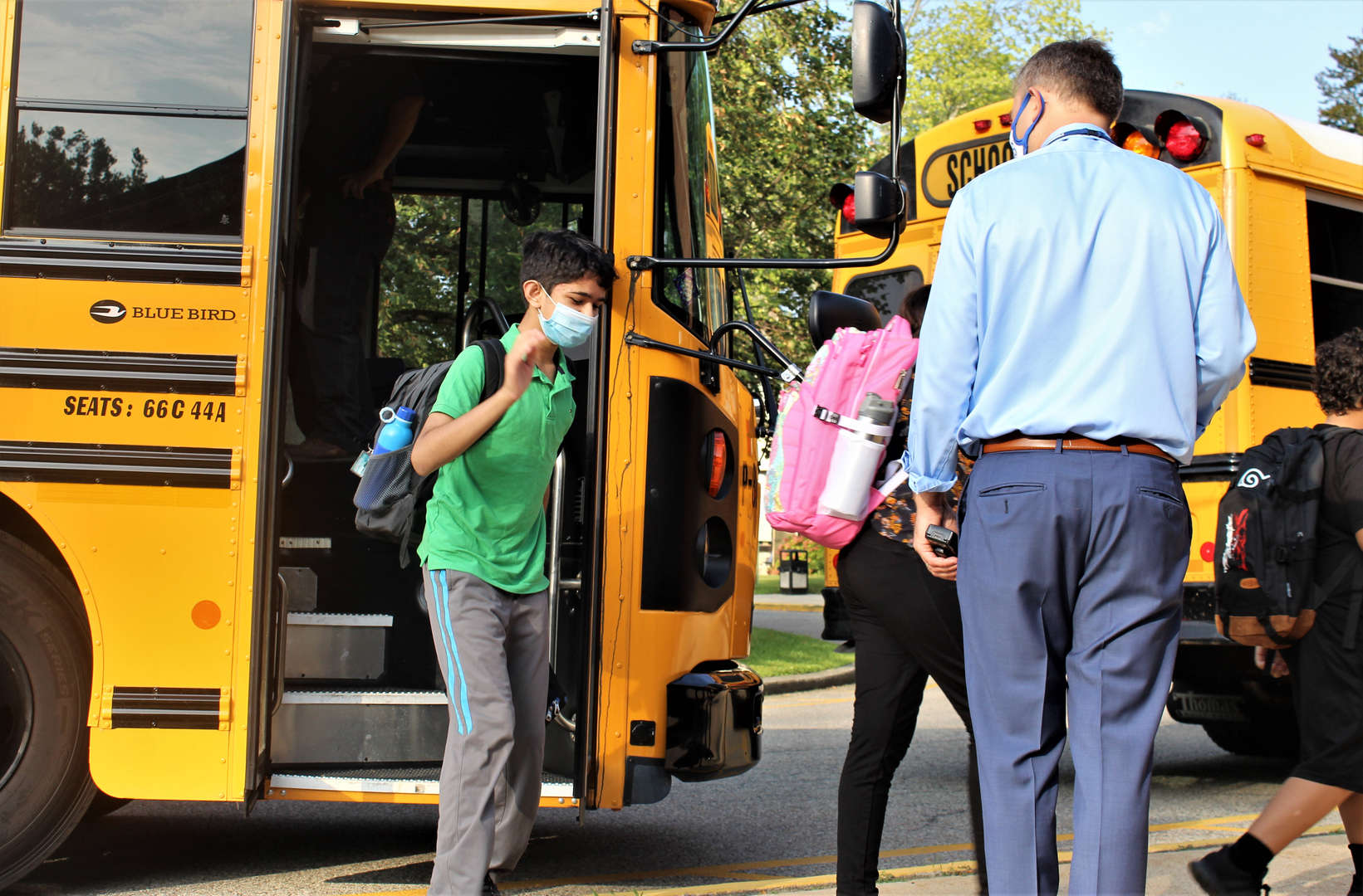 Principal Adam Brown welcomes students getting off their bus on the first day of school.