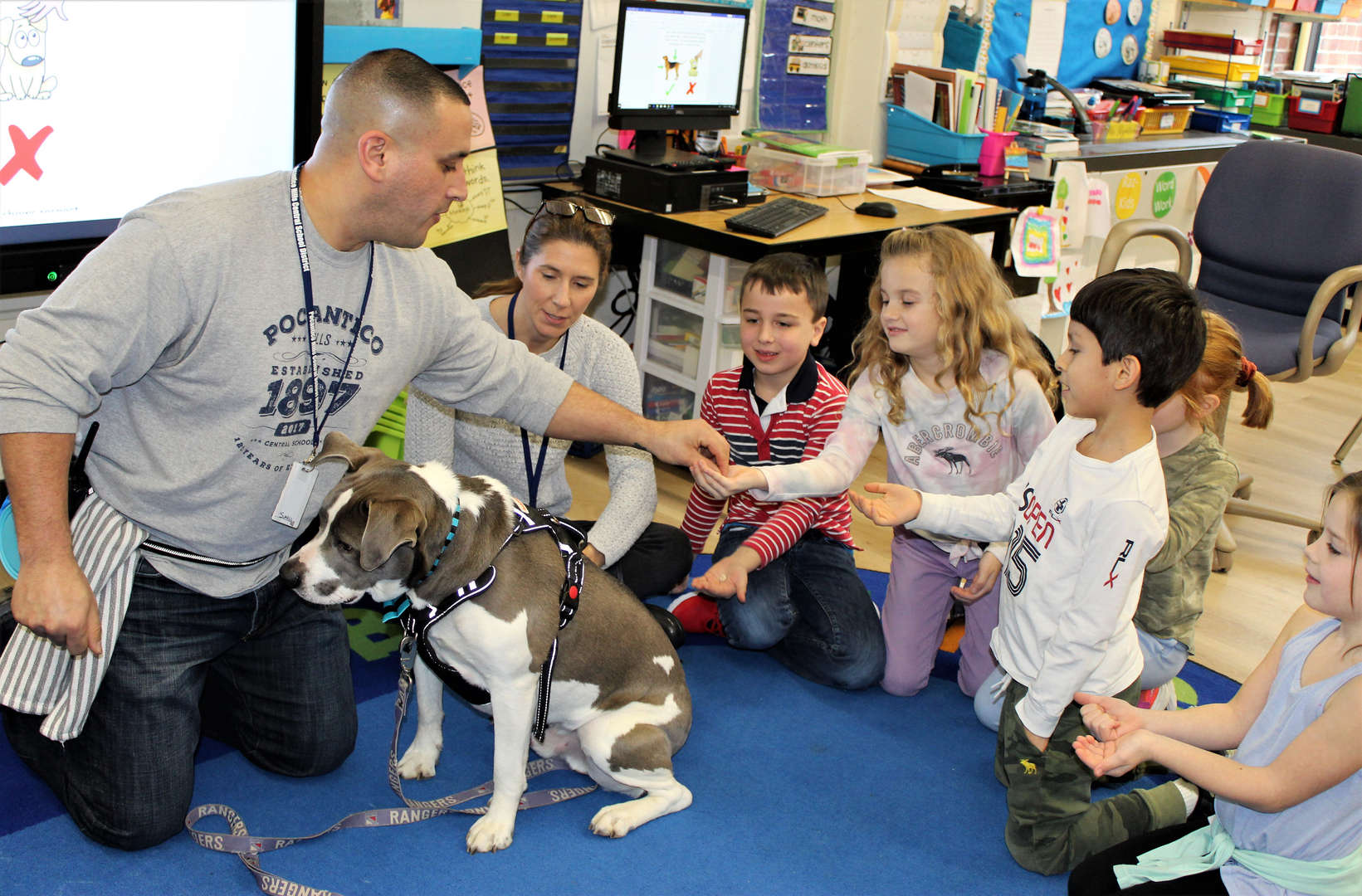 A teacher introduces a new therapy dog to first-graders.