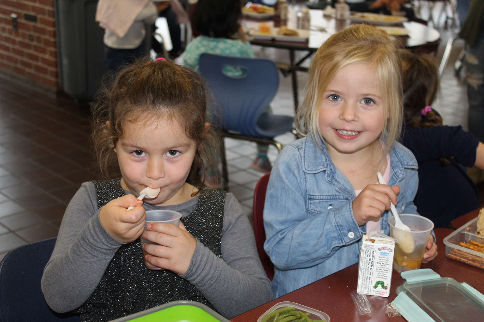 Two girls eat soup in the school cafeteria.