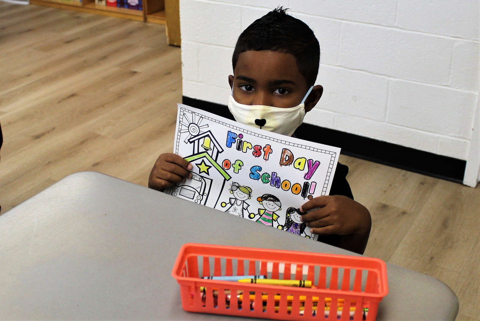 """A boy holds up a """"first day of school"""" worksheet that he colored."""