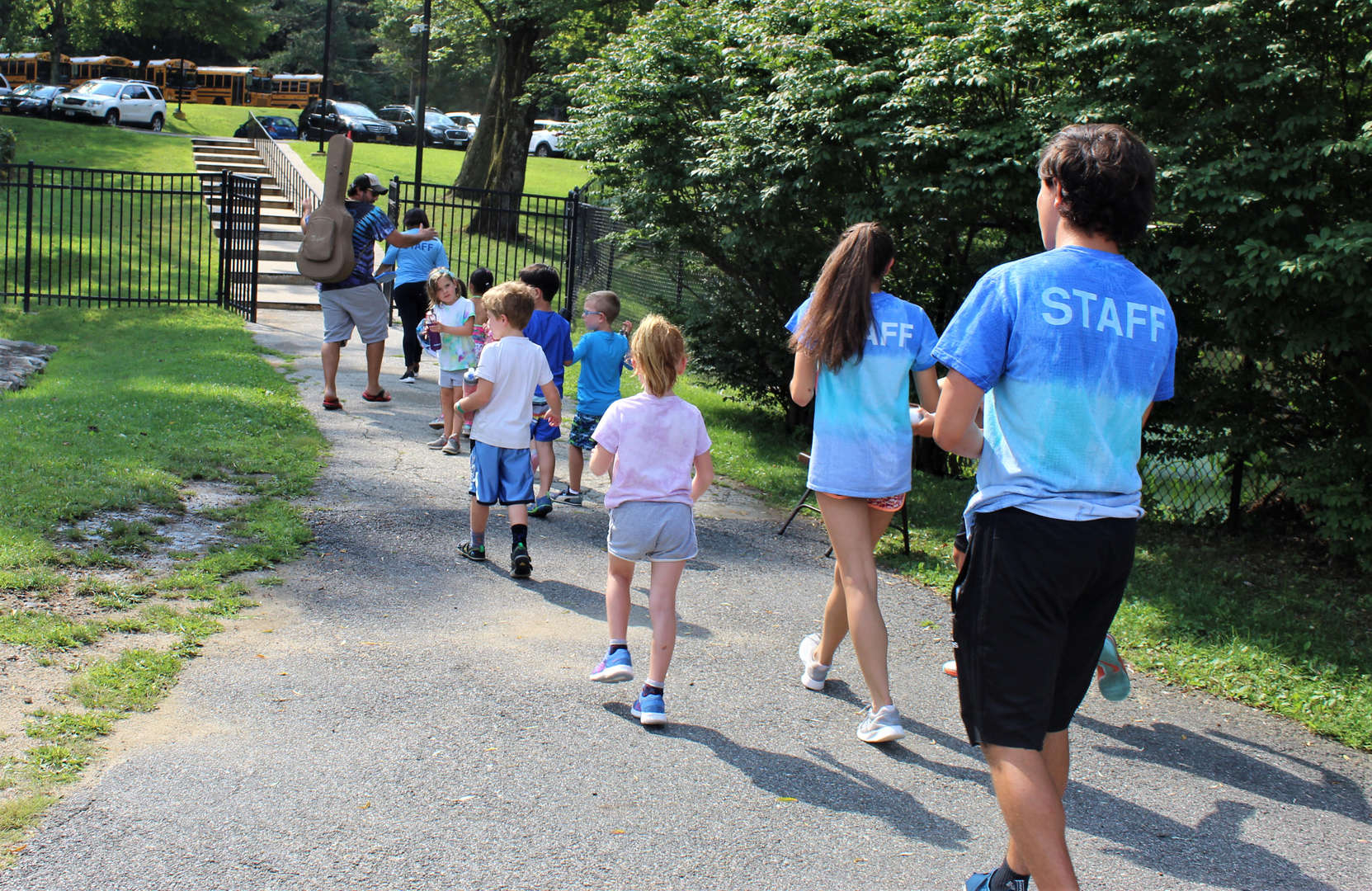 Children and camp counselors going on a hike.