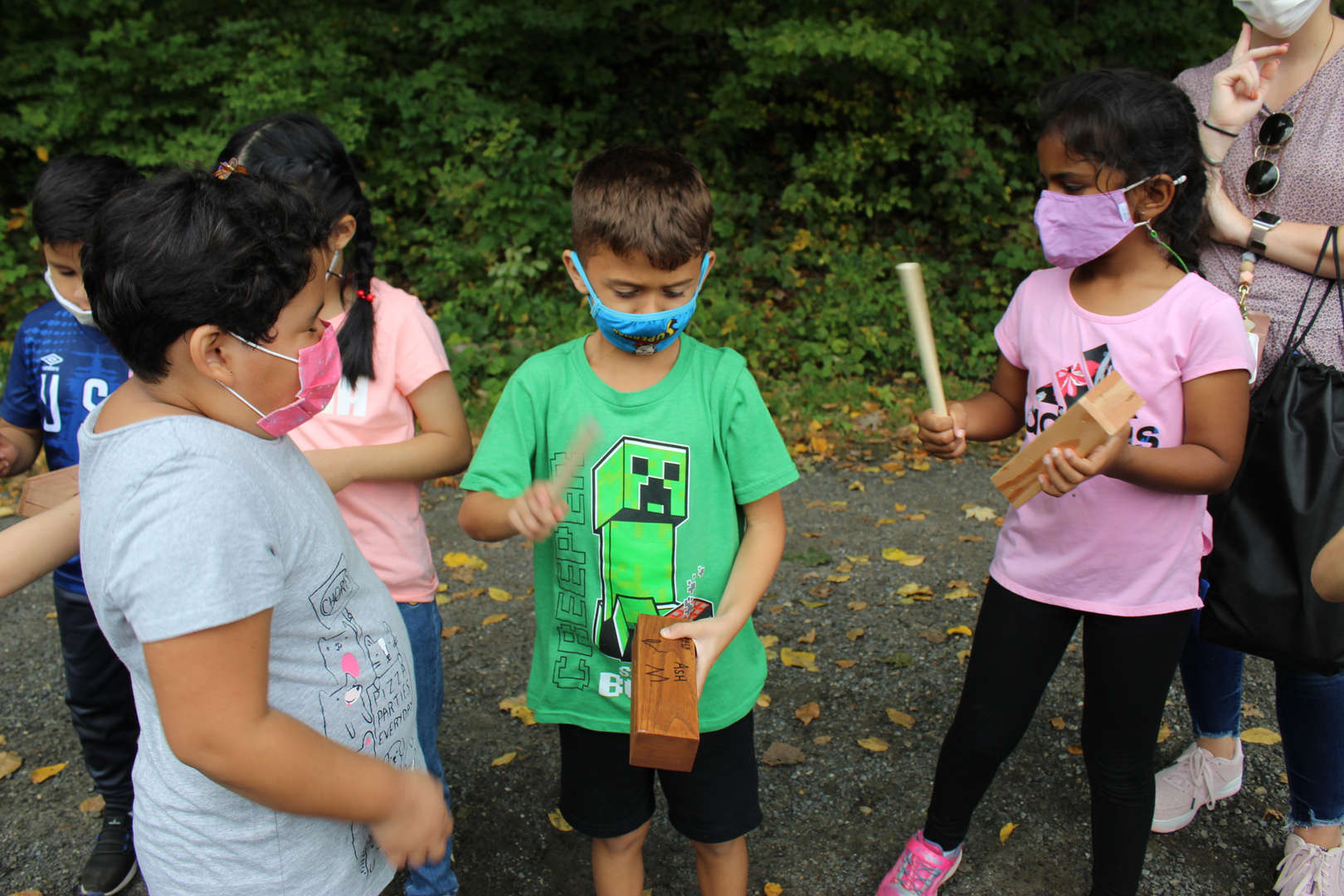 Pocantico Hills students compared sounds that different types of wood made when hit with a stick.
