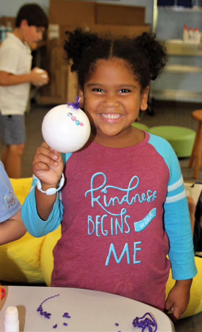 A first-grader displays art she created with a Styrofoam ball.