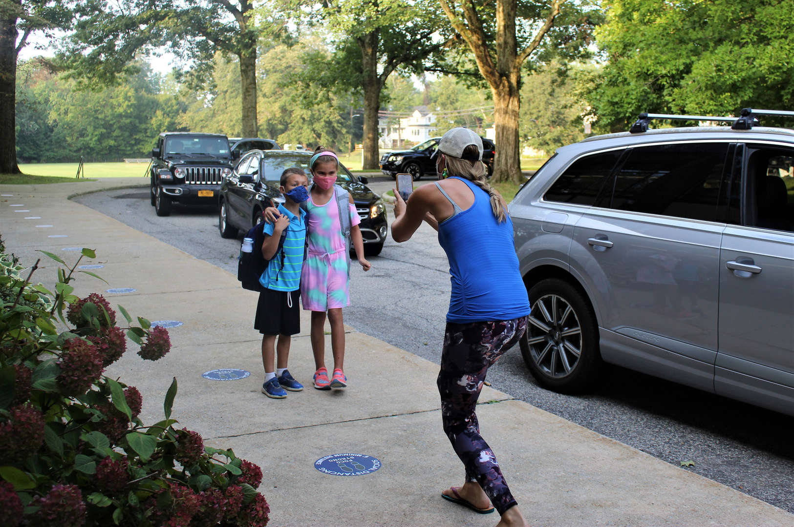 A mother takes a photo of her son and daughter on the first day of school.