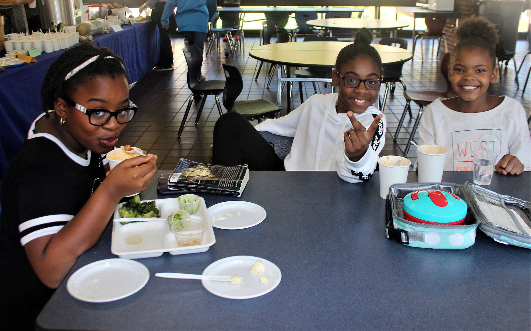 Three girls are eating soup in the cafeteria.