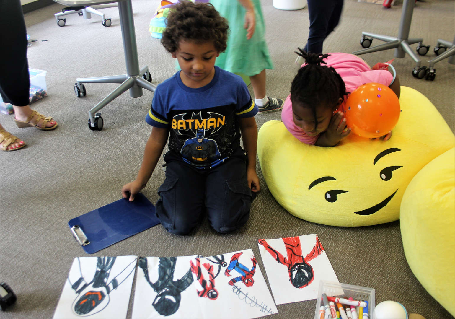 A first-grader displays his superhero artwork in the Makerspace.