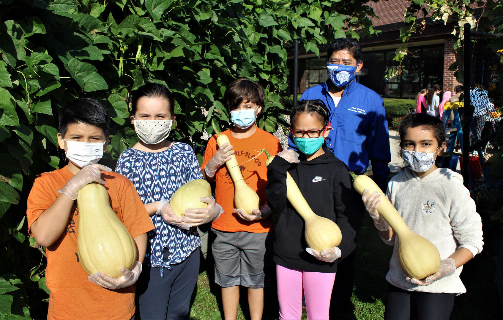 Five students and custodian and gardener Jose Zamora gather squash from the garden on Harvest Day.