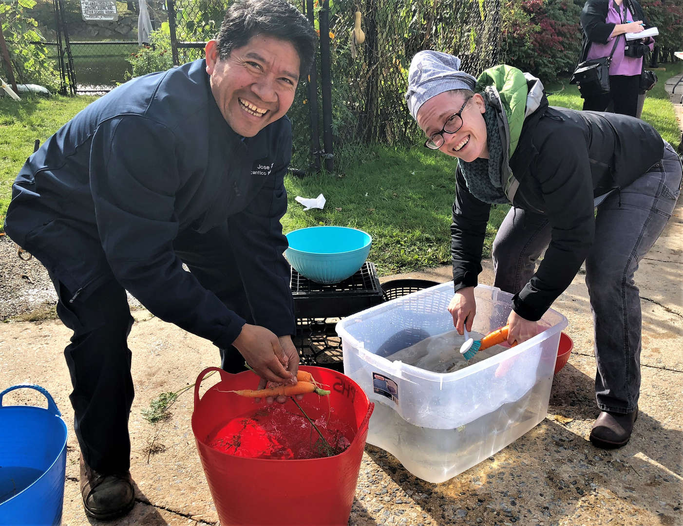 Gardener Jose Zamora and Chef Kassie Arcate clean carrots in buckets of water.