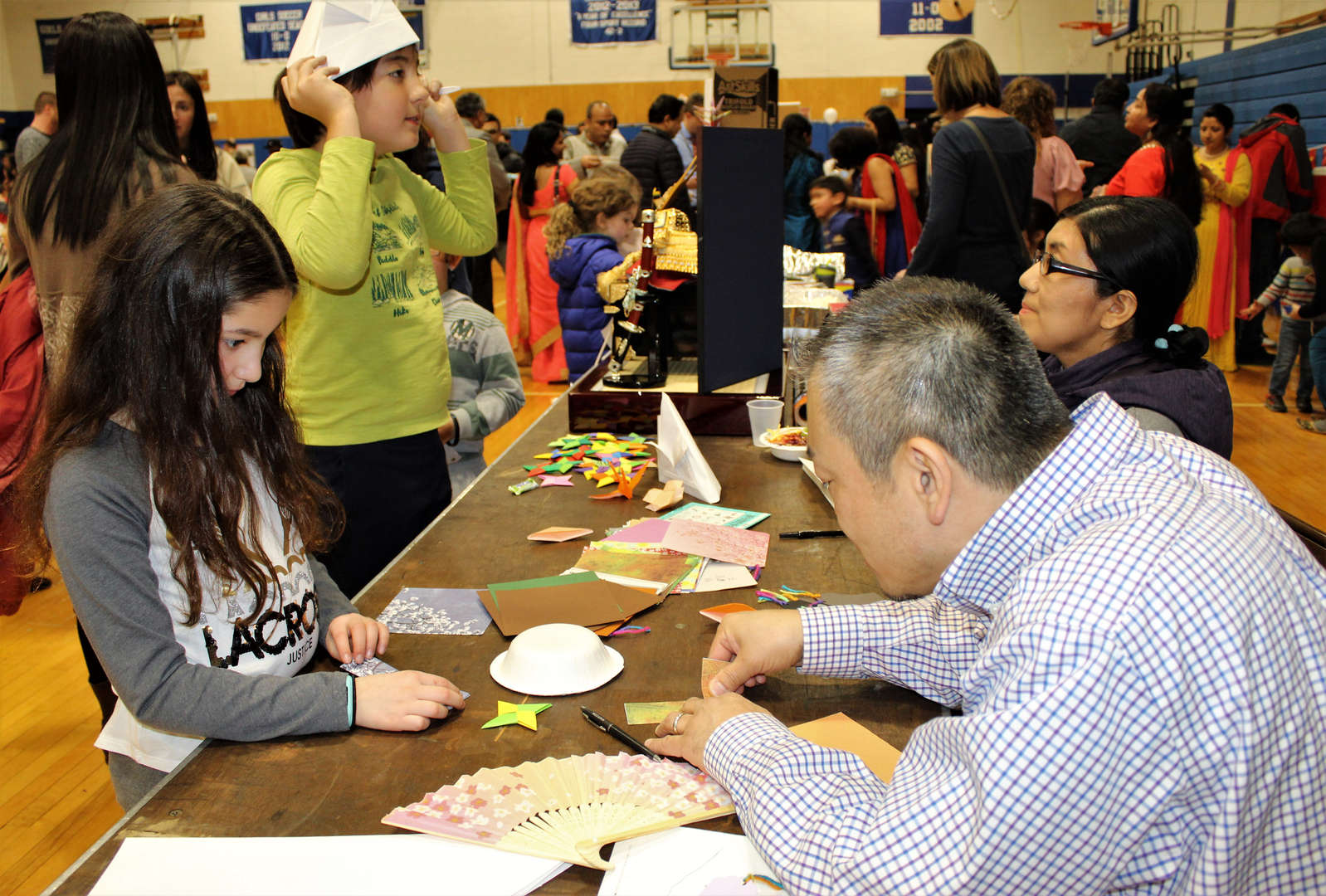 A grandparent teaches a student origami during One World Evening.