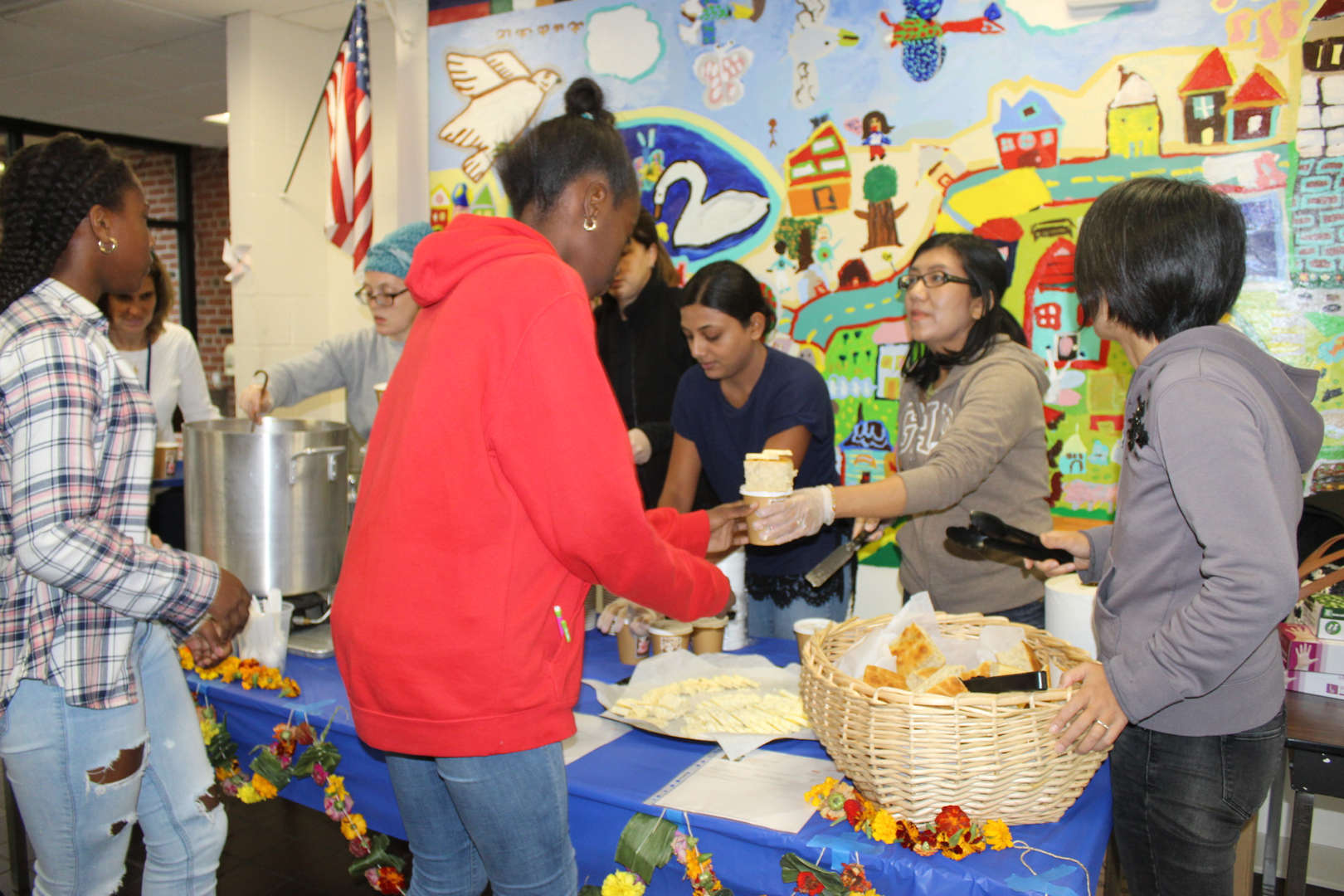 Parents serve soup to children in the school cafeteria.