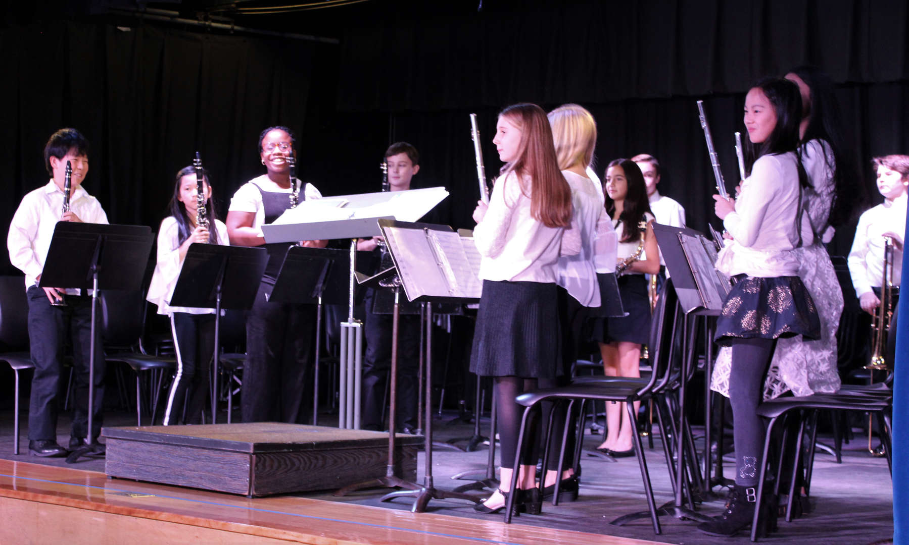 The Sixth Grade Band stands as the audience claps for its Winter Concert performance.
