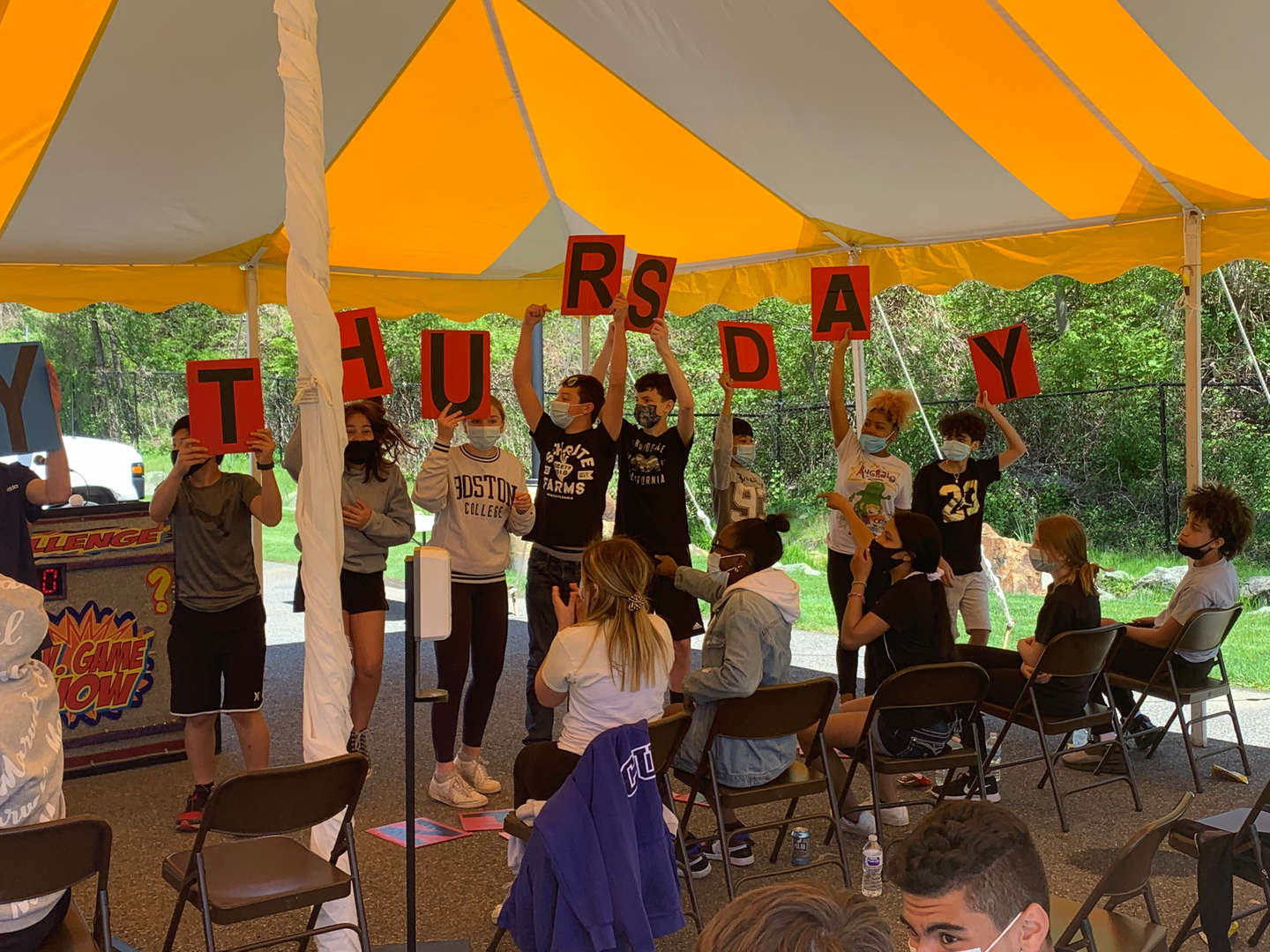 Eighth-graders hold up signs that spell out Thursday during a game show on campus.