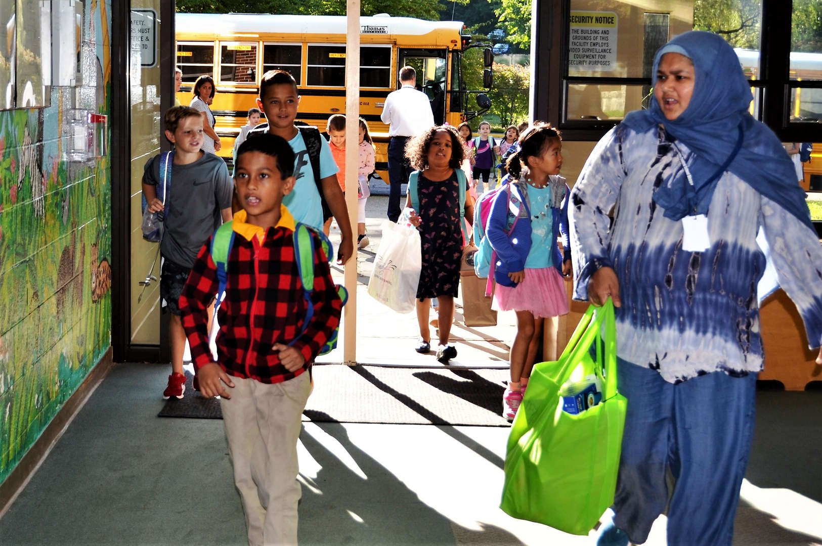 Students walk into the school after getting off the bus.