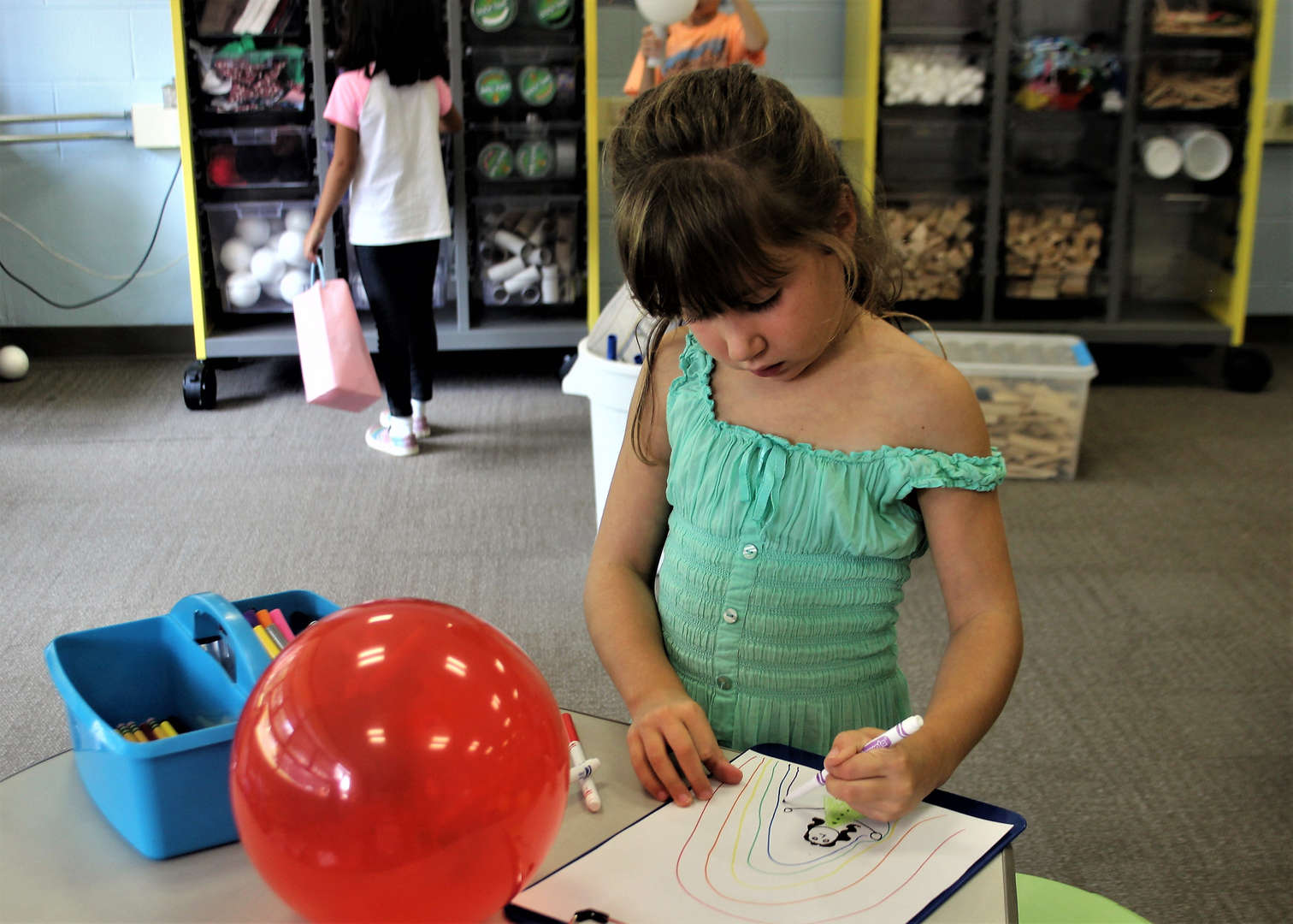 A first-grader draws with markers during a Makerspace class.