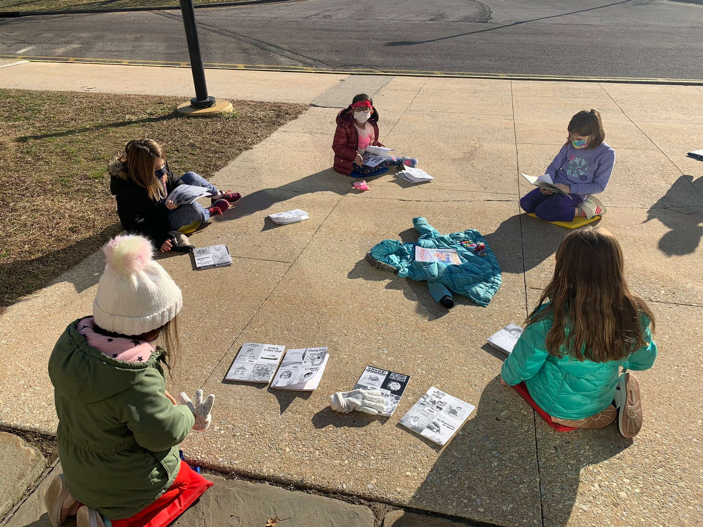 A group of young students reading books outside.