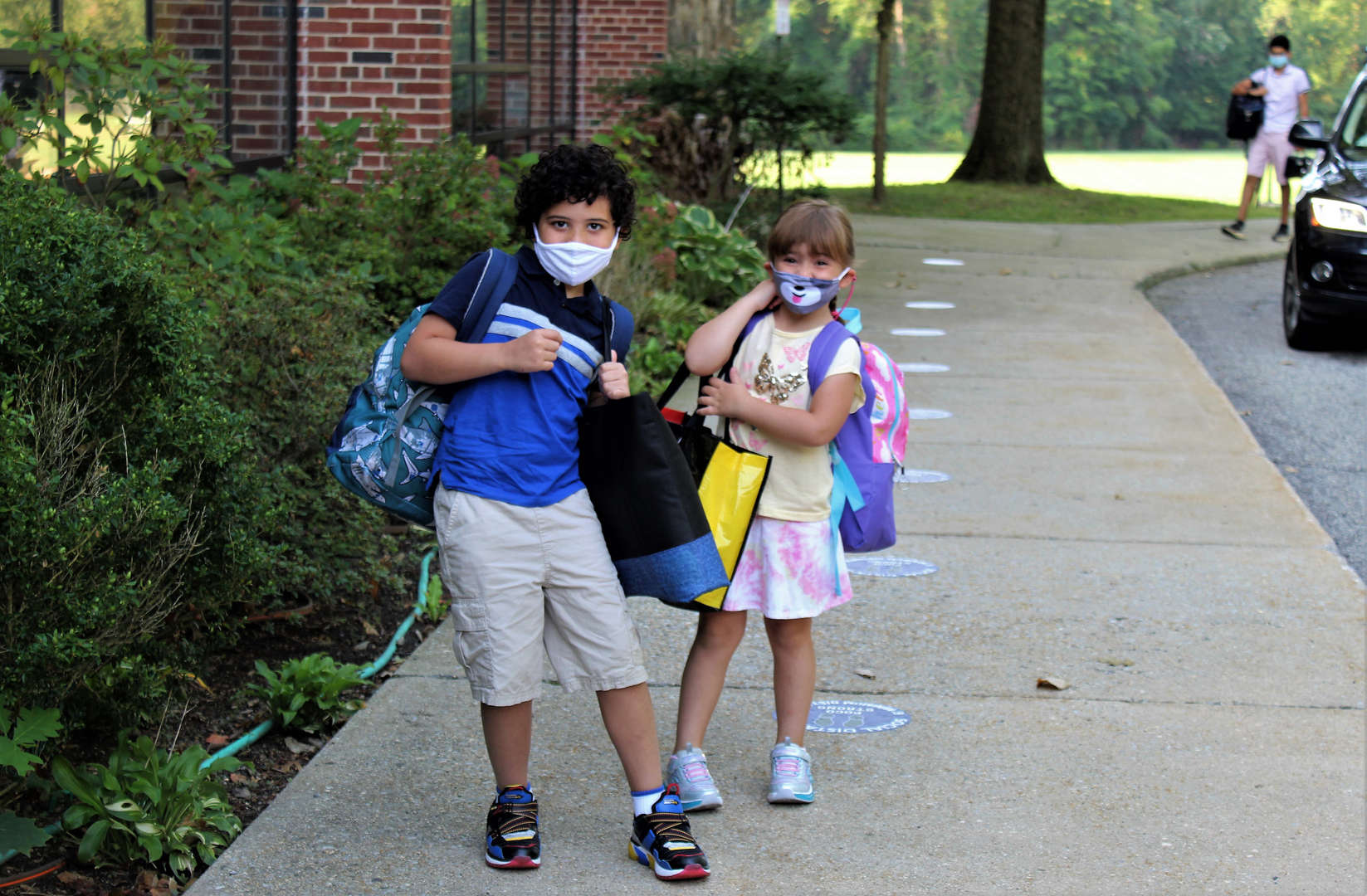 A brother and sister pause for a photo while walking into school the first day.