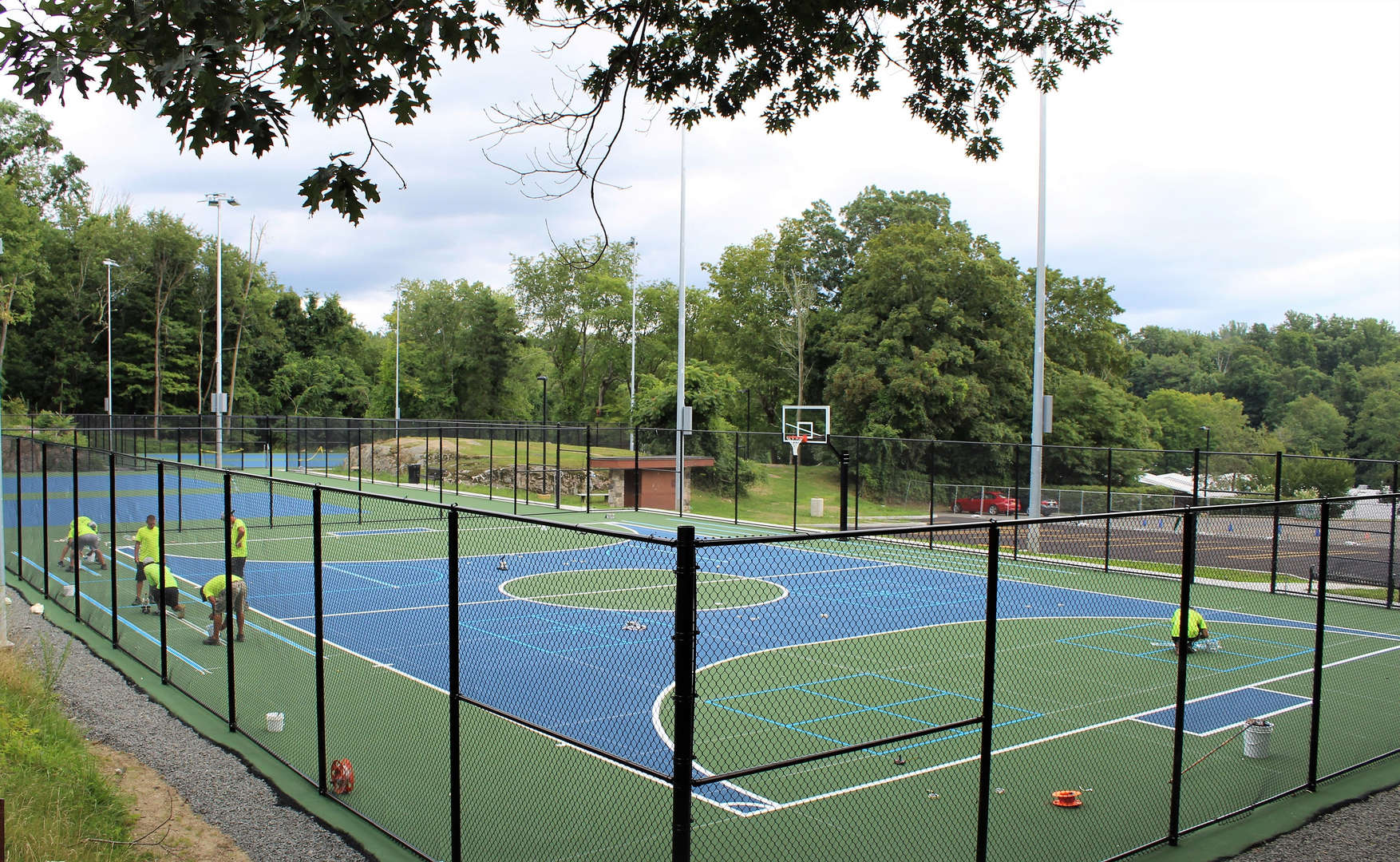 A crew paints a new tennis court.