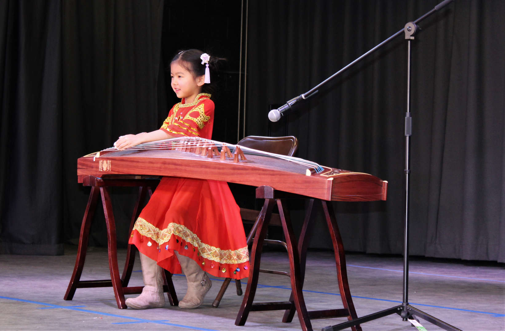 A female student plays the Chinese harp during One World Evening.