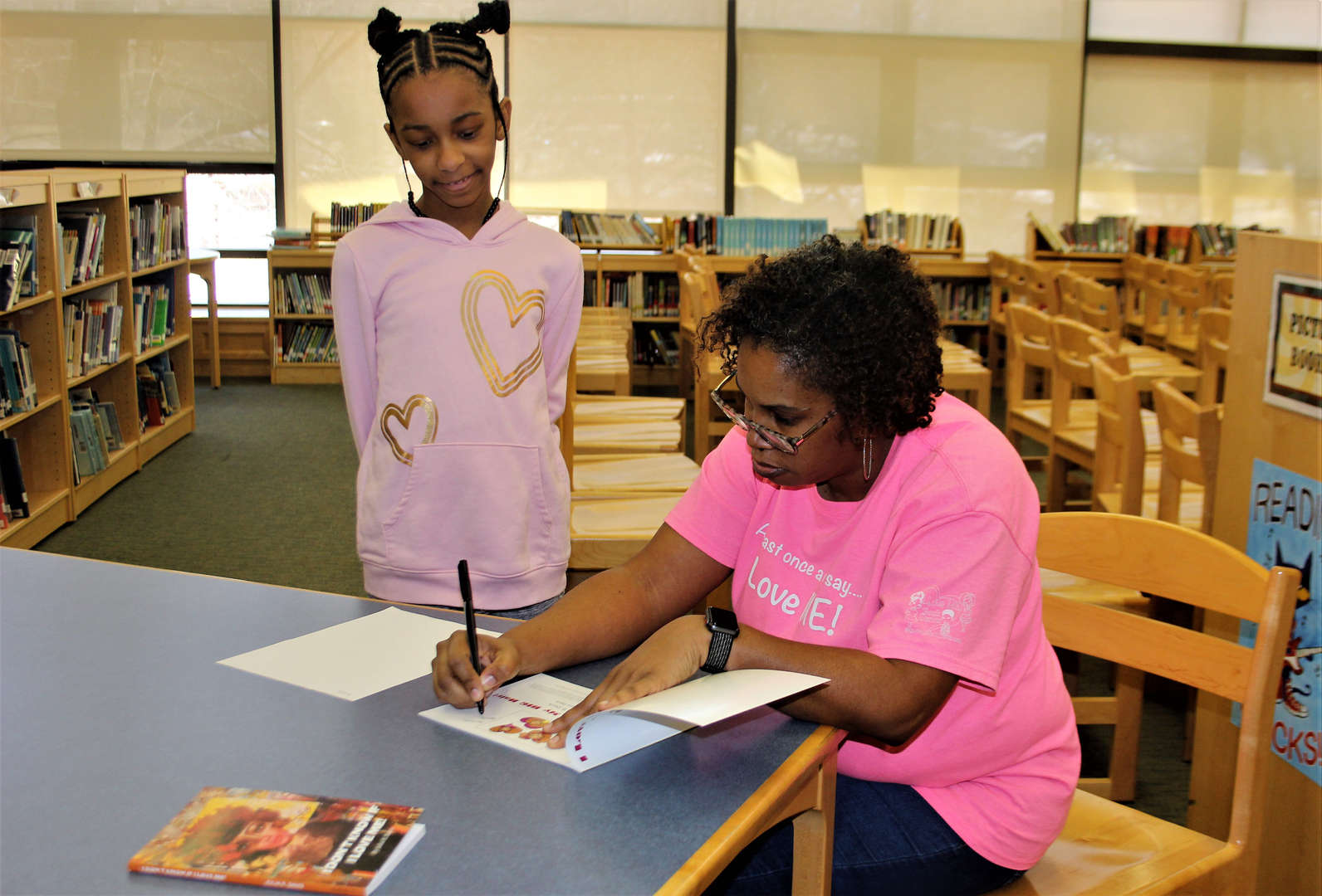 Author Julia Davis signs one of her books for a student.