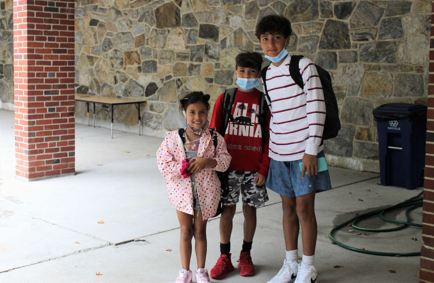 Three siblings pose for a photo before entering school.