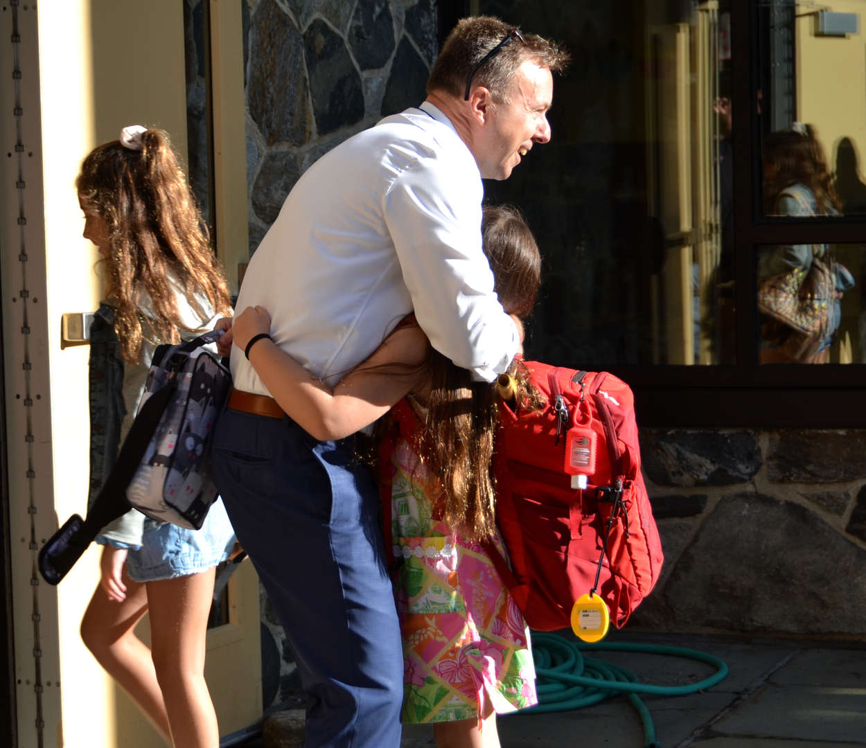 Principal Adam Brown hugs a student on her first day back.