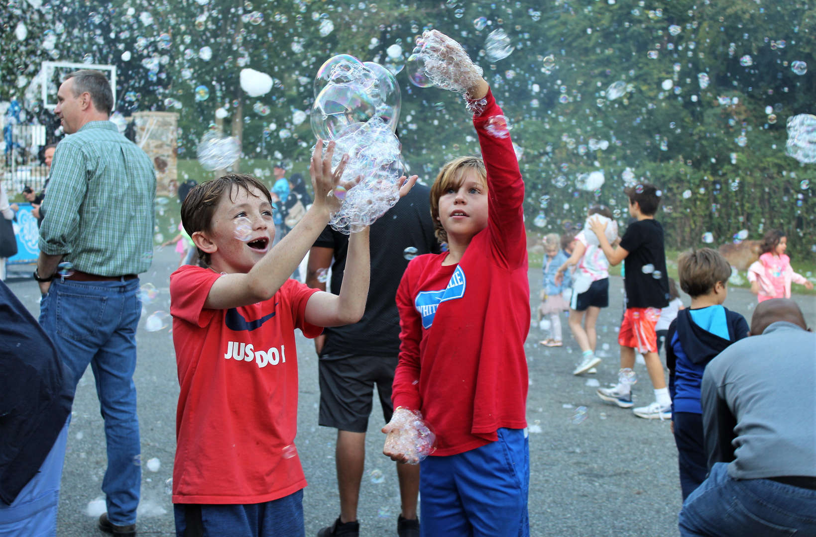 Two boys are collecting bubbles from the Bubble Bus.