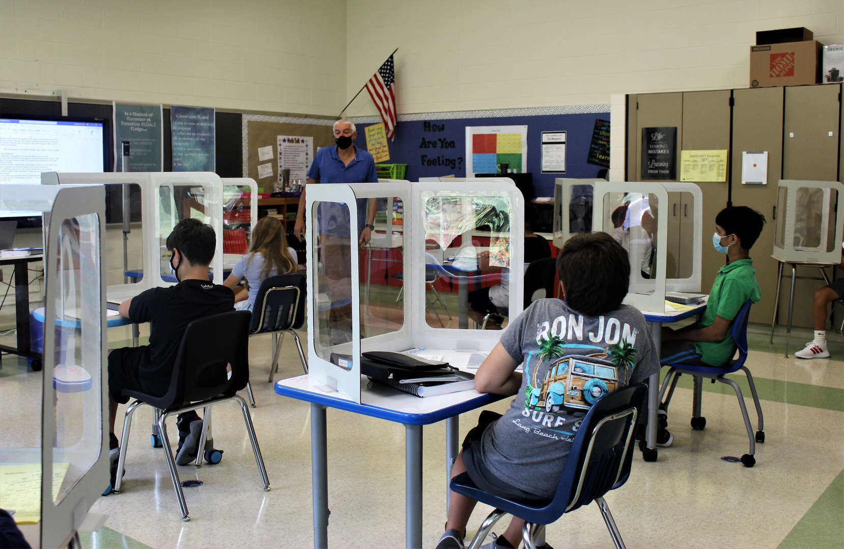 Science teacher Vincent Cook speaks to students on the first day as everyone adjusts to the new three-sided carrels with see-through panels atop everyone's desk.