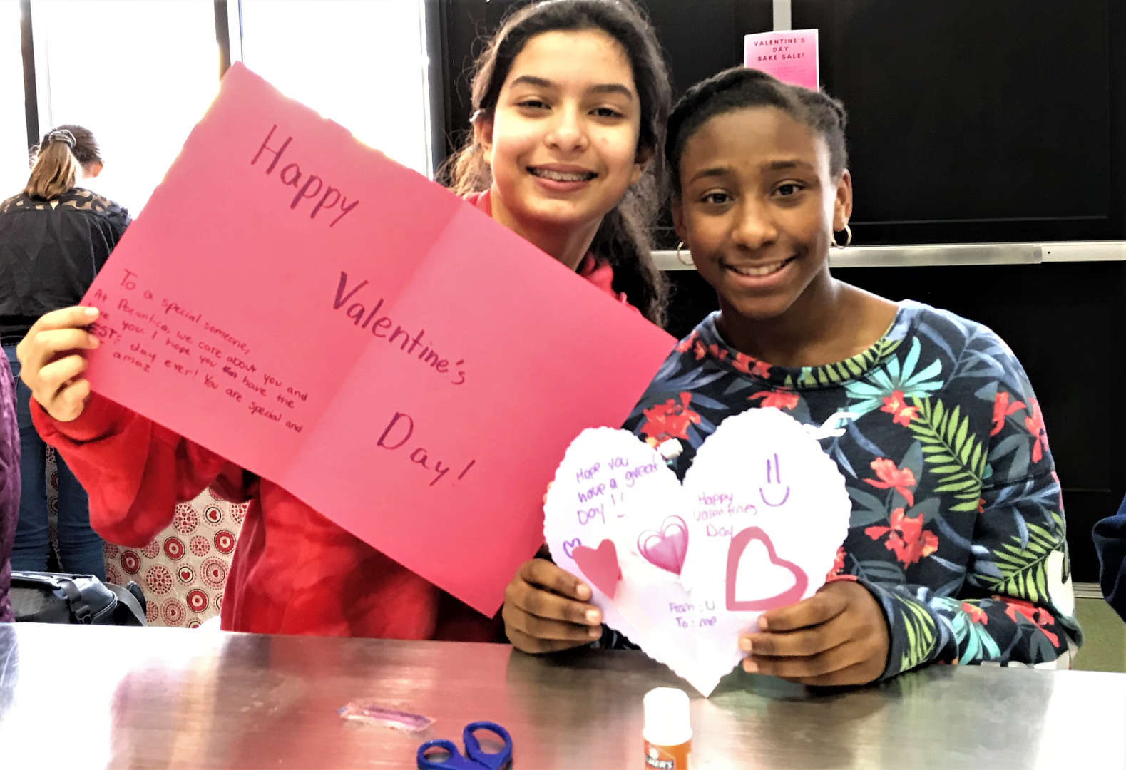 Two students display the Valentine's Day cards they made.