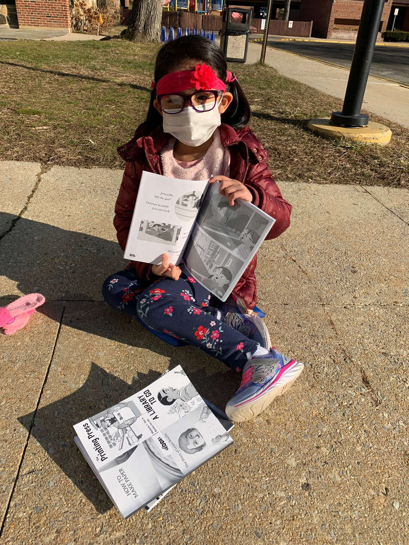A girl shows off the book she is reading outside.