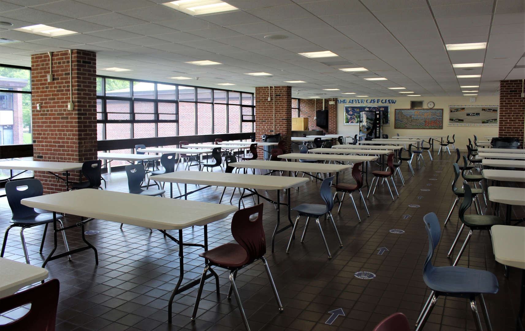 Photo of the cafeteria, with long tables and room for two students only.