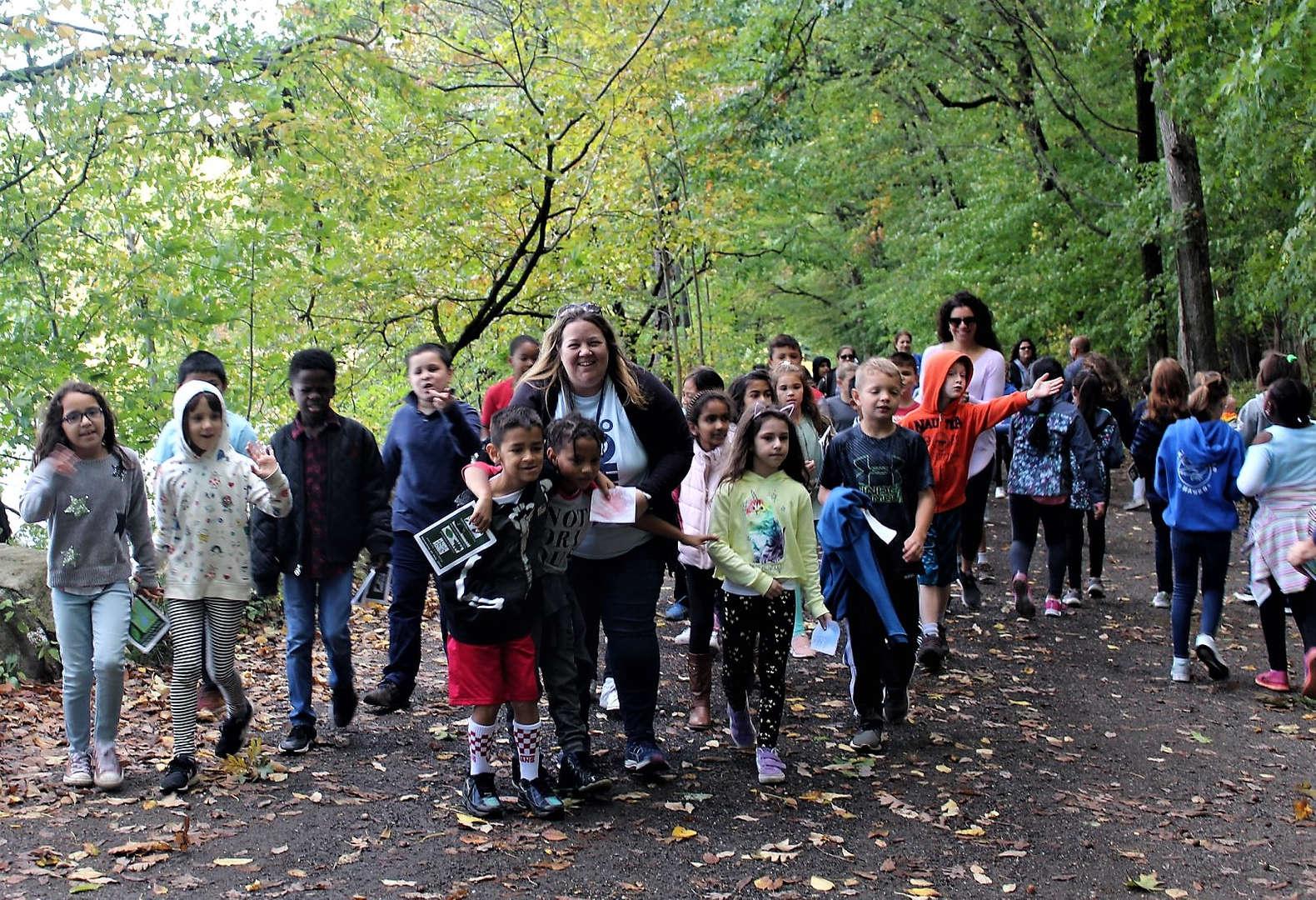 Third-grade teacher Kerry Papa walks around Swan Lake with her class.