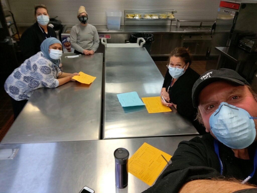 Cafeteria workers who continue to prepare meal kits