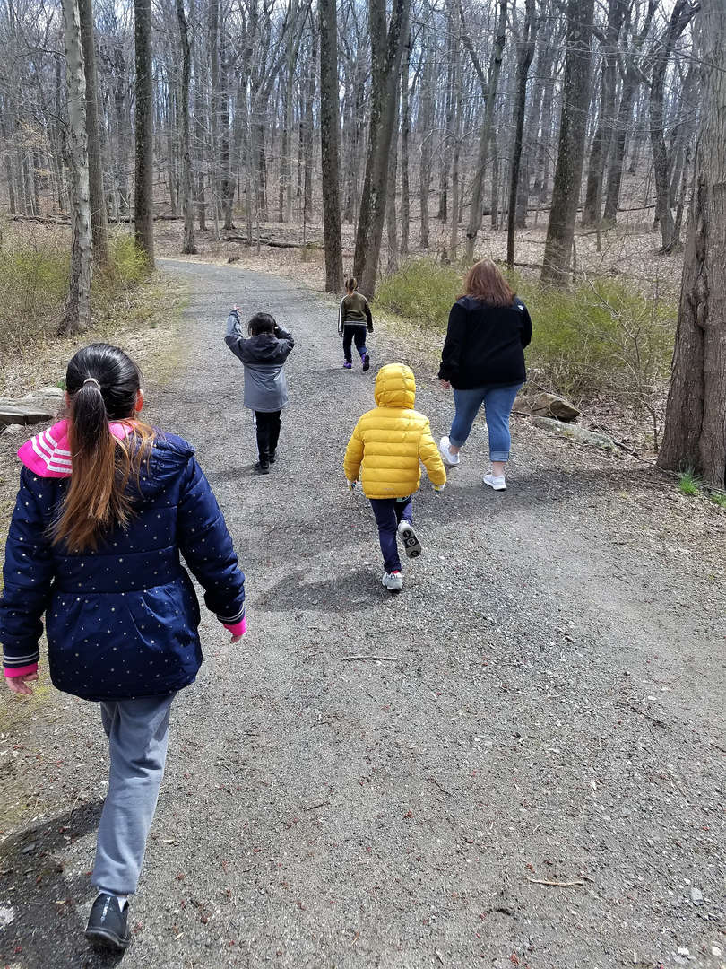 Children in the childcare program at Pocantico walk on a path behind the school.