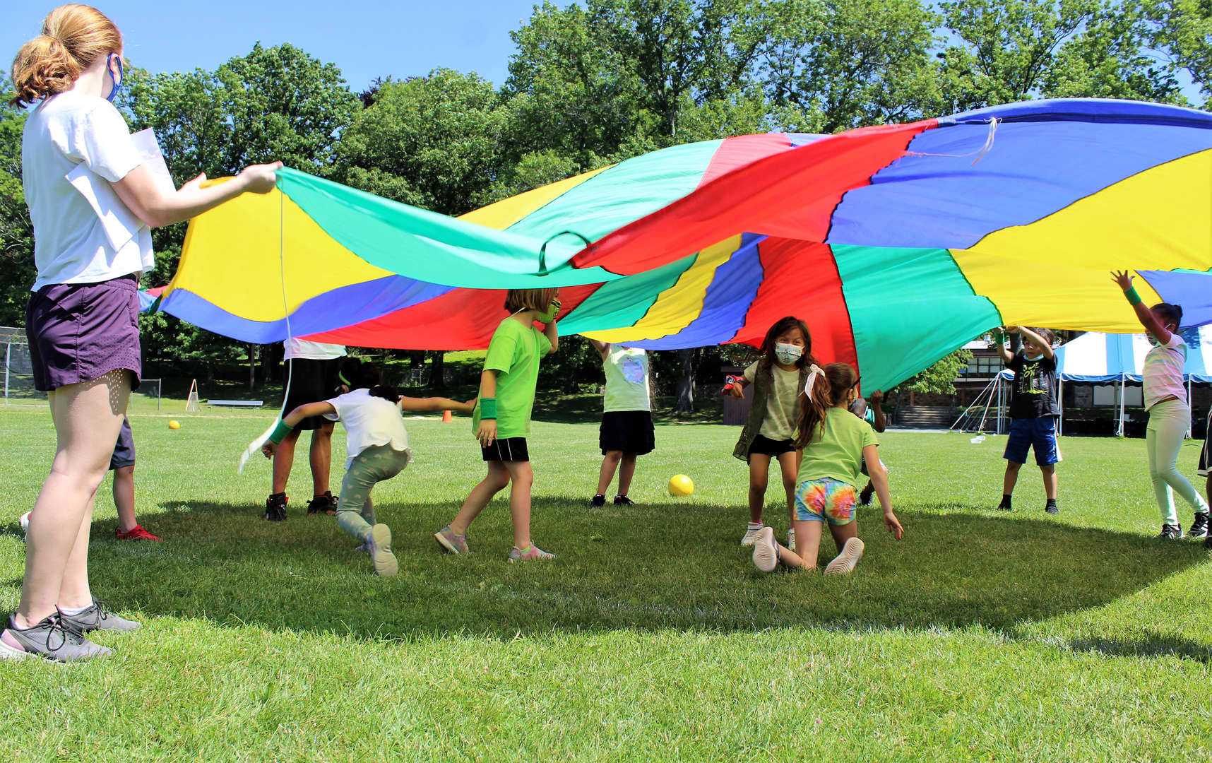 Students playing a game with a colorful parachute.