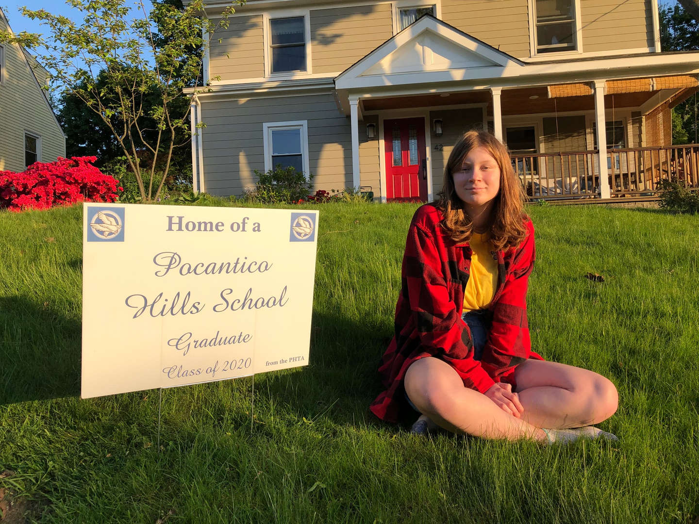 "An eighth-grade girl poses with a ""Pocantico Hills School Graduate"" sign."
