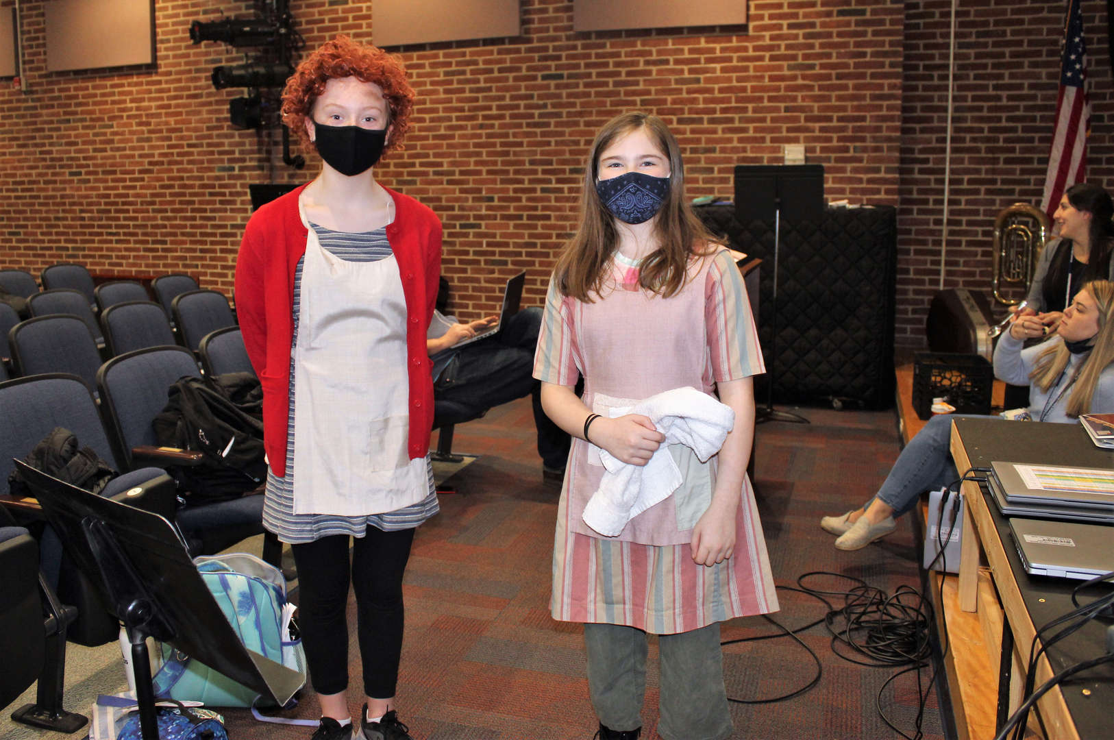Two female students are dressed for their parts: Annie and another orphan.