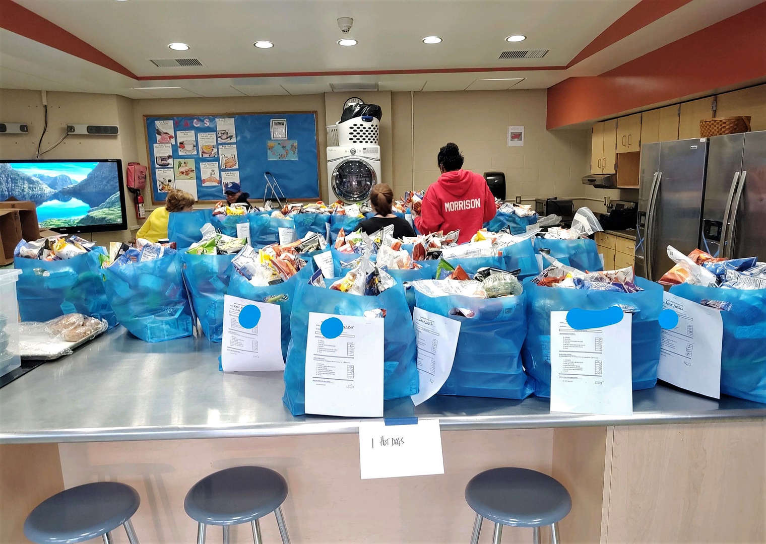 Cafeteria workers pack bags of food for school families who need it.