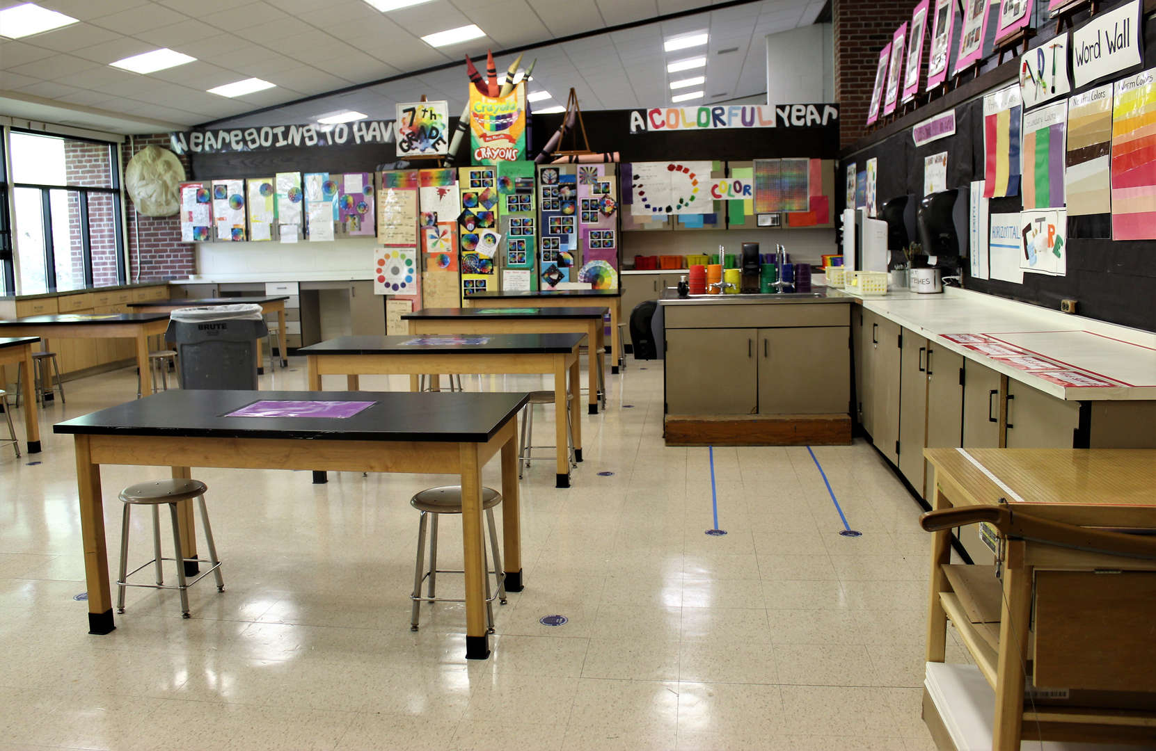 Photo of the art classroom, with social distancing stickers and less furniture.