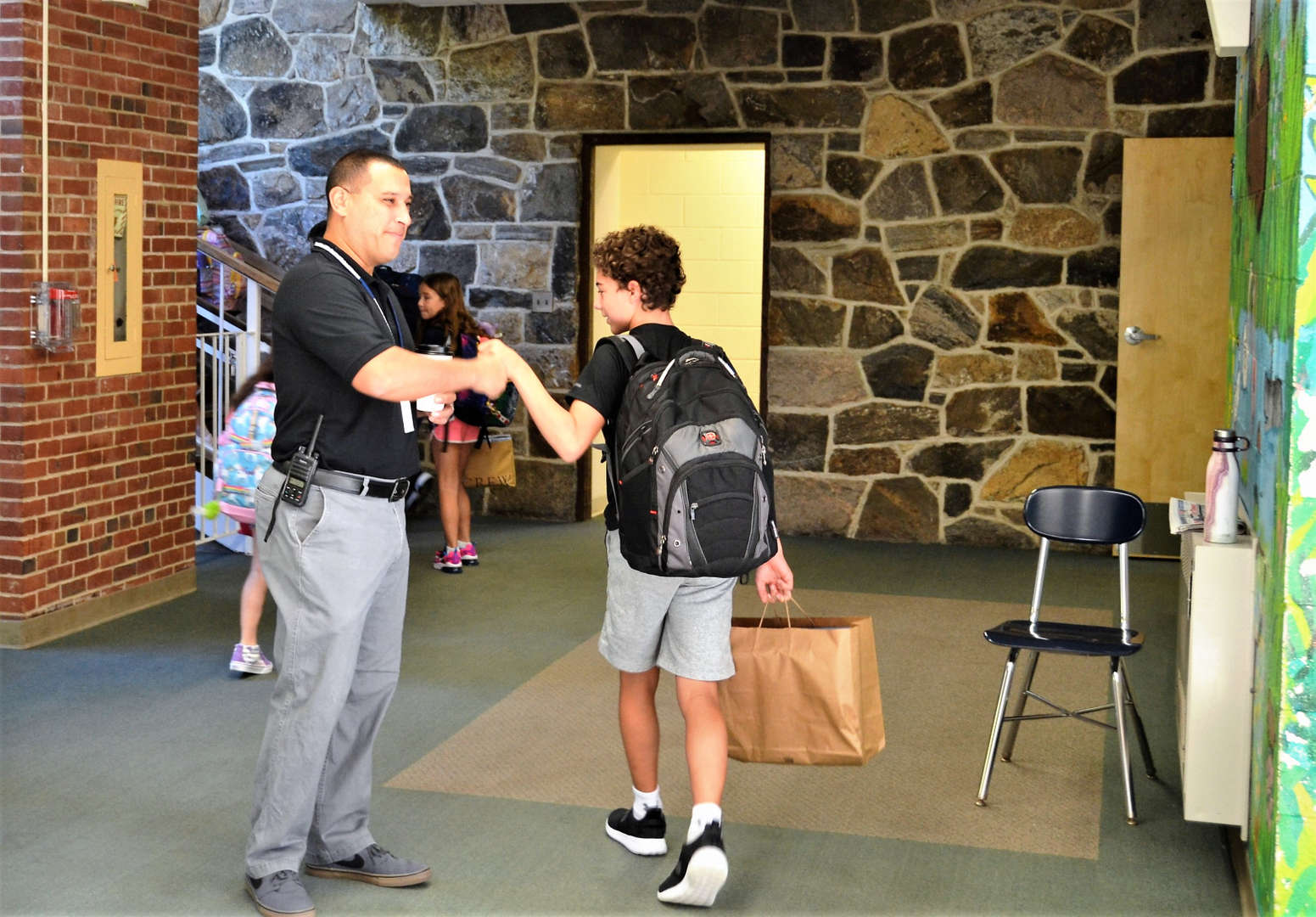 A staff member greets a student on the first day of school.