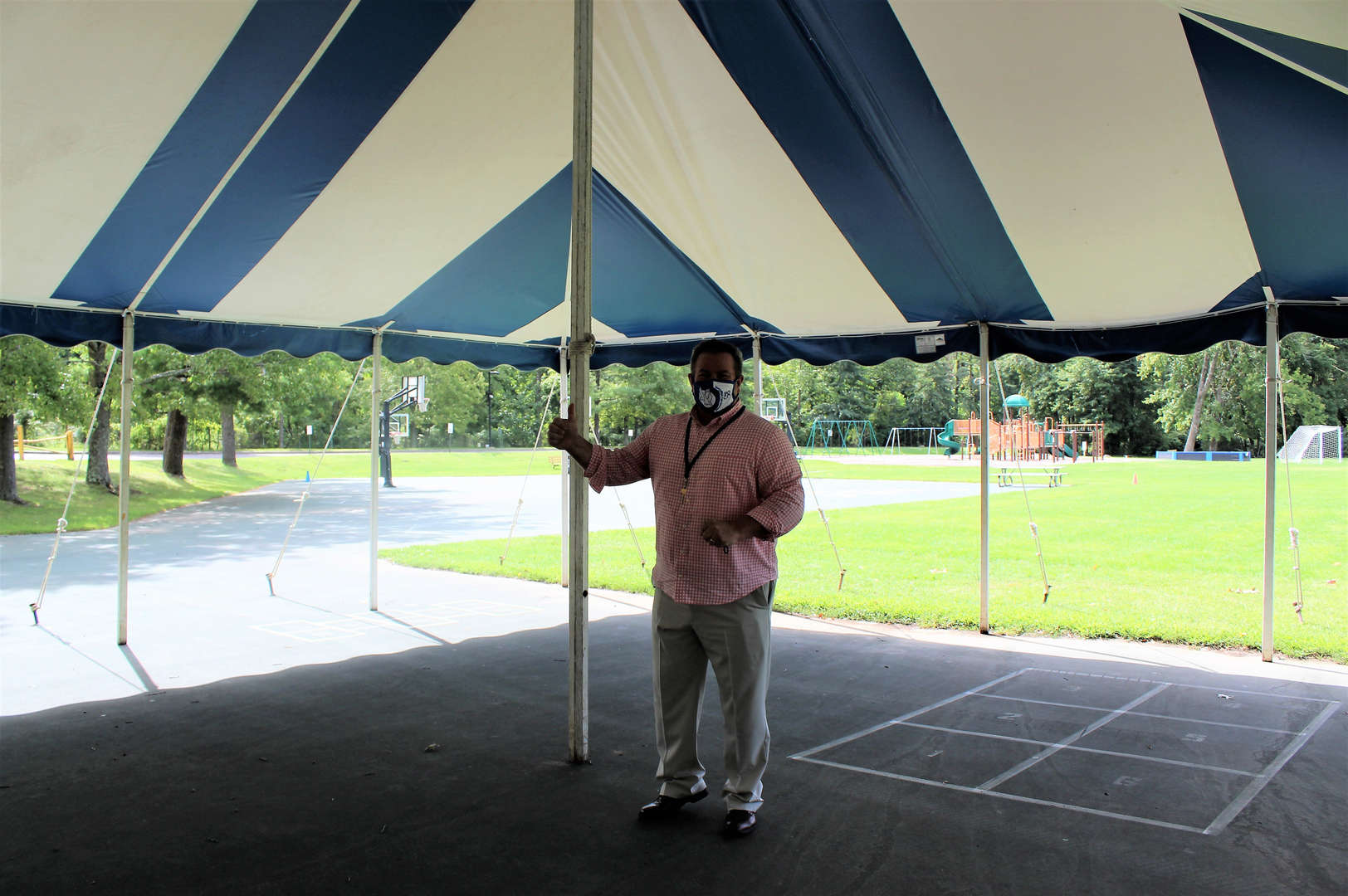 Superintendent Richard Calkins gives a thumbs-up as he stands in a tent outside the school.