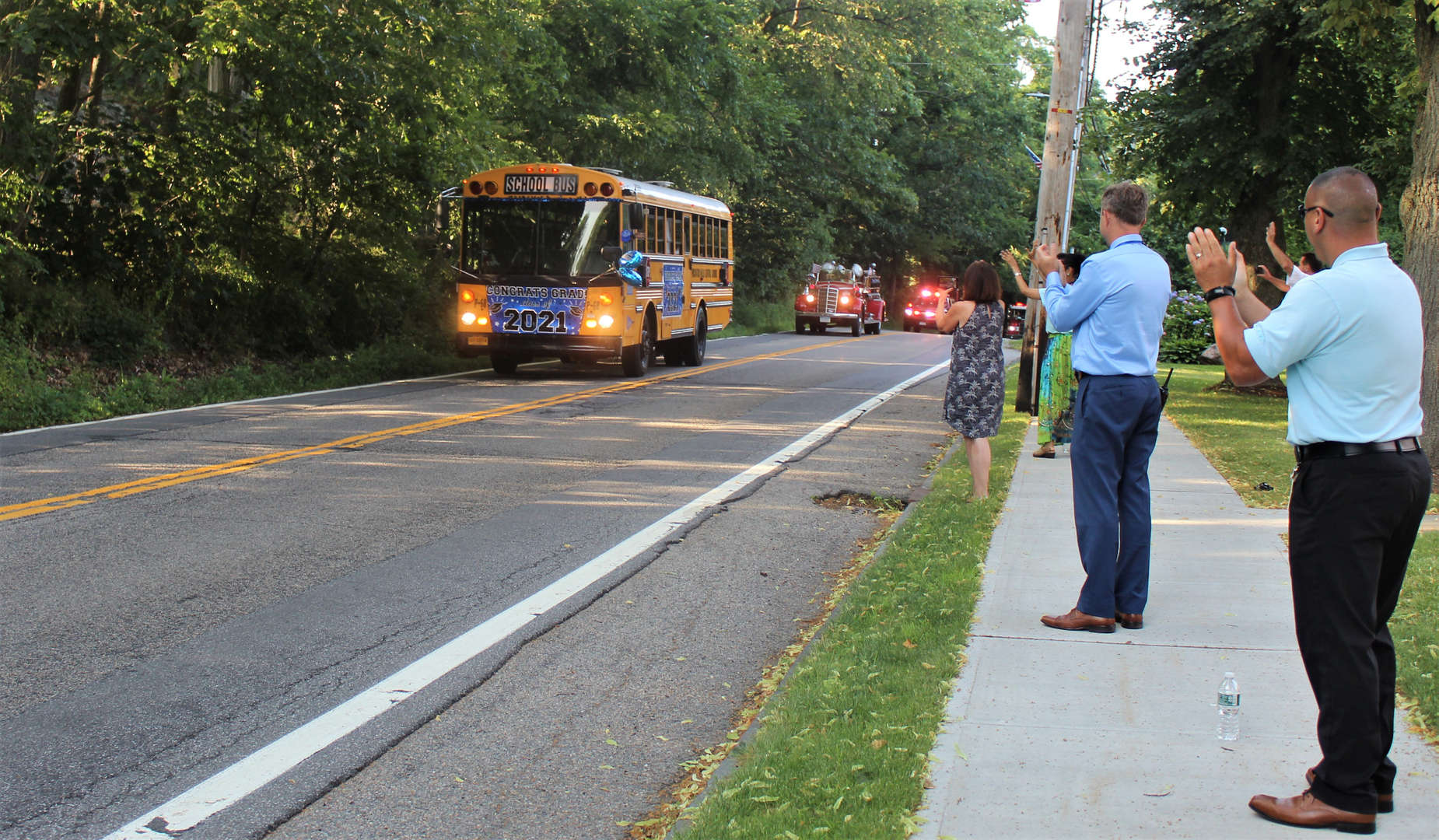 Staff members wave to car parade in front of the school.