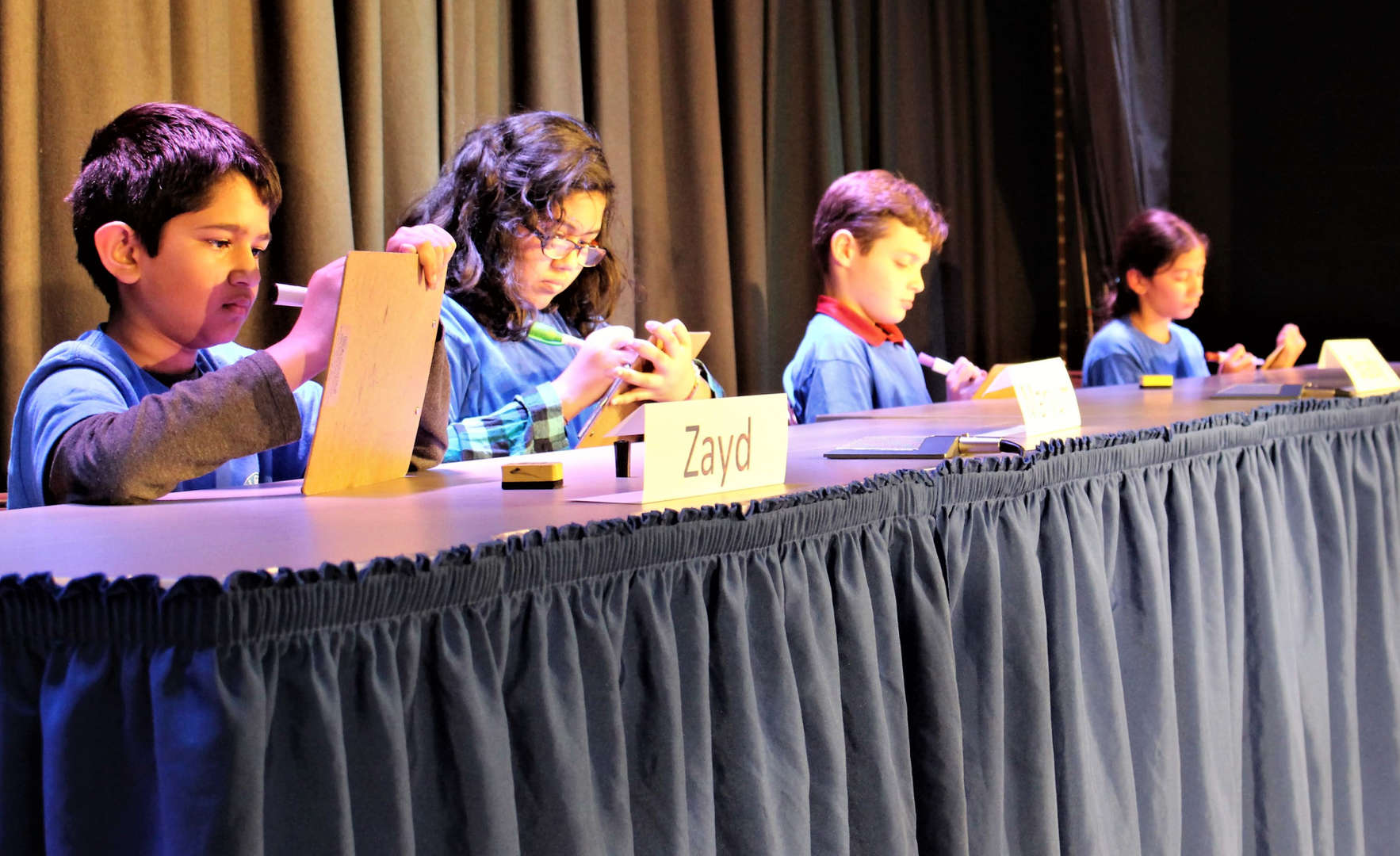 GeoBee contestants write down their answers on whiteboards.