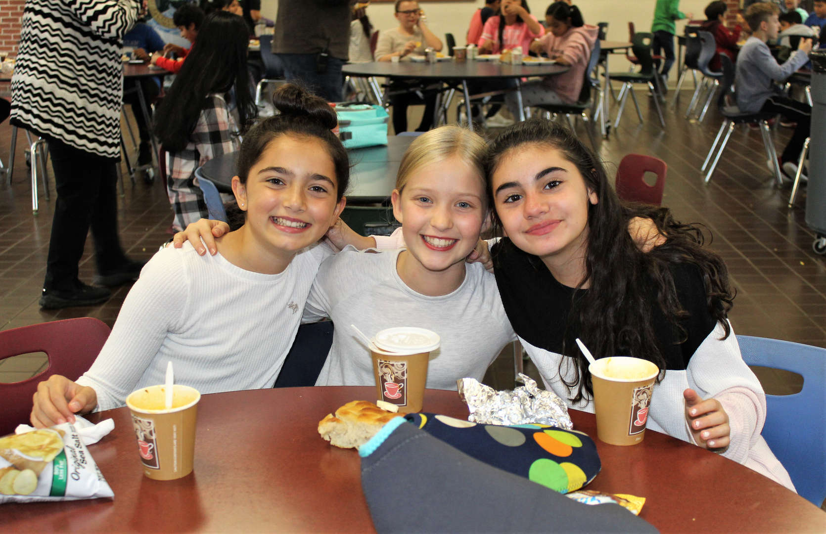 Three girls eat soup in the cafeteria.